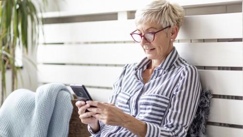 Eine ältere Frau schaut auf ihr Smartphone.