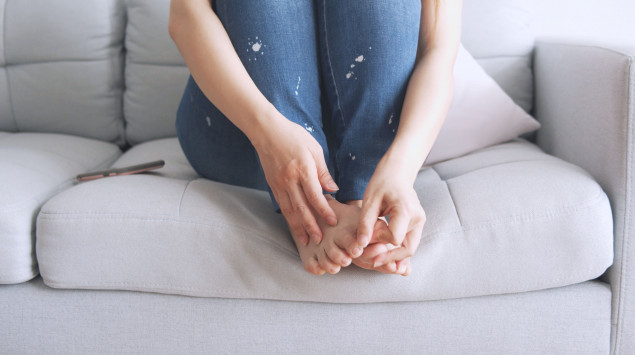 Flöhe in der Wohnung: Eine Frau sitzt mit angezogenen Beinen auf dem Sofa.