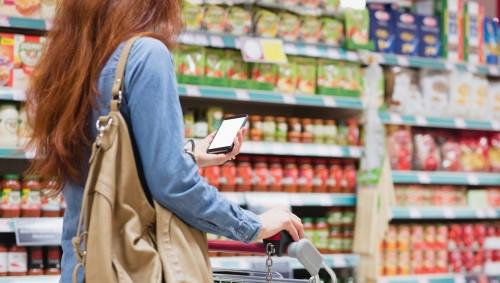 Eine Frau schiebt im Supermarkt einen Einkaufswagen vor sich her und schaut aufs Smartphone.