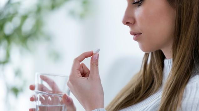 Eine Frau blickt auf eine Tablette in der linken Hand und hält ein Wasserglas in der rechten Hand.