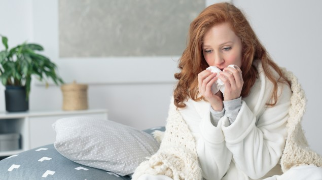 Eine krank aussehende Frau schneuzt sich: Eine Erkältung ist oft harmlos, eine Grippe kann dagegen wesentlich schwerer verlaufen.