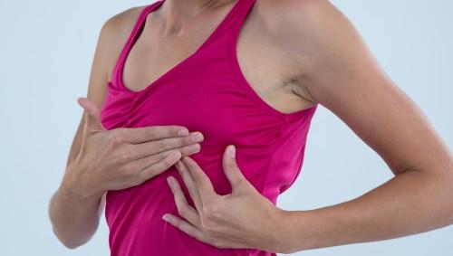 Eine Frau untersucht ihre Brust auf Veränderungen.