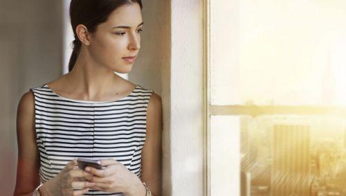 Eine Frau schaut nachdenklich aus dem Fenster, in den Händen hält sie ihr Handy.