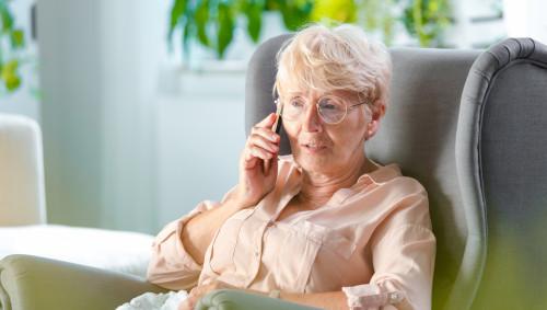Eine Frau telefoniert und sitzt dabei in einem Sessel.