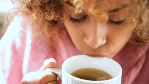 Eine junge Frau nippt an einer Tasse Tee.
