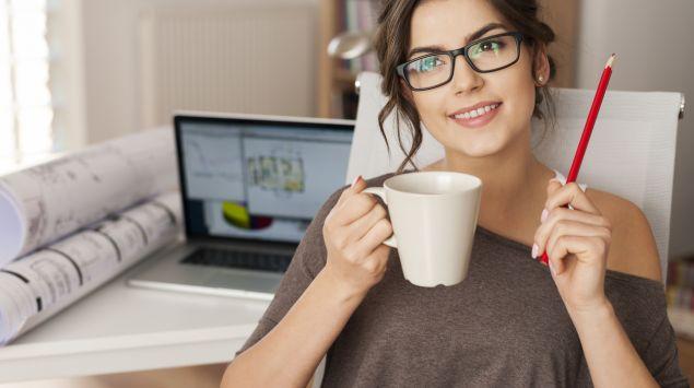 Eine Frau sitzt neben Ihrem Laptop und überlegt.