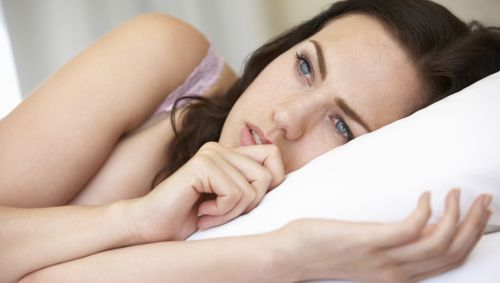 Eine Frau liegt unruhig im Bett.