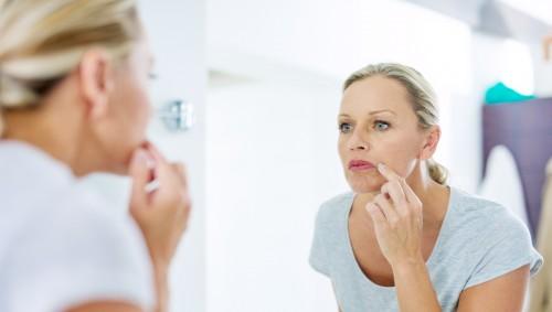 Eine Frau schaut prüfend in den Spiegel.