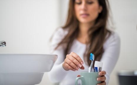 Parodontitis: Eine Frau greift nach einer Zahnbürste.