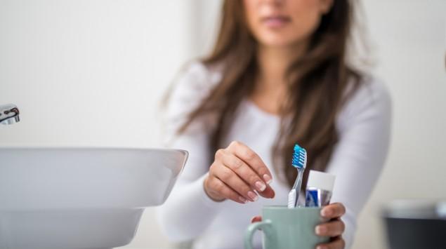 Eine Frau greift nach einer Zahnbürste.