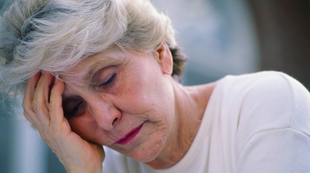 Eine ältere Frau stützt müde den Kopf auf.