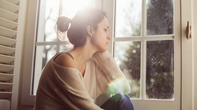 Eine Frau sitzt alleine am Fenster.