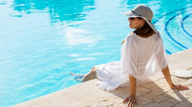 Eine Frau mit Sonnenhut, Sonnenbrille und luftigem Oberteil sitzt an einem Swimmingpool.