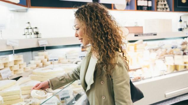 Eine Frau steht an der Käsetheke eines Supermarkts.