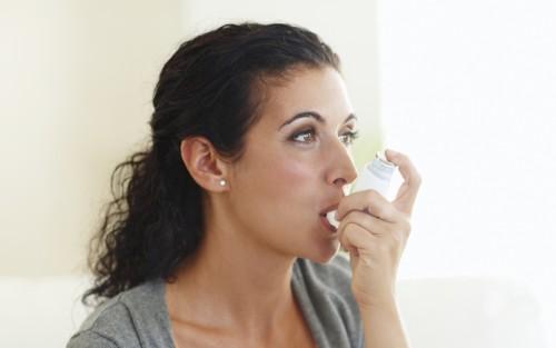 Das Bild zeigt eine junge Frau, die ein Asthmaspray benutzt.
