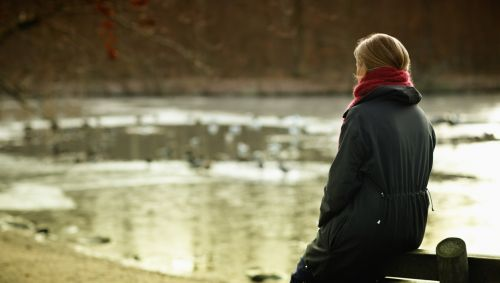 Eine winterlich gekleidete Frau sitzt auf der Lehne einer Bank am Ufer eines Sees.
