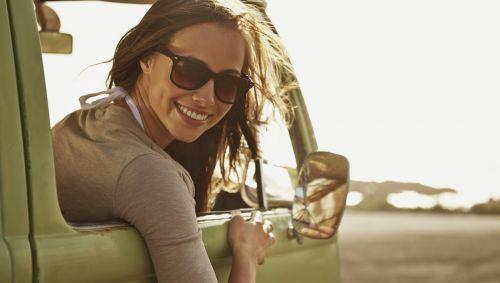 Eine junge Frau lehnt sich lachend aus dem Beifahrerfenster eines Autos.