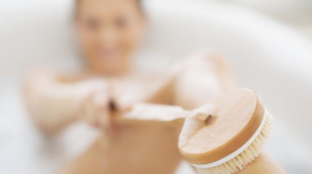 Eine Frau liegt in der Badewanne und streicht mit einer Badebürste über ihren Unterschenkel.
