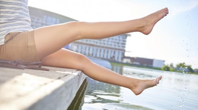 Das Bild zeigt eine Frau, die ihre Füße ins Wasser hält.