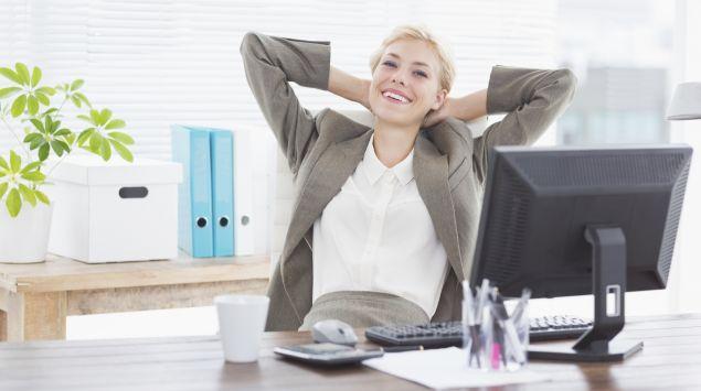 Eine junge Frau sitzt entspannt und lächelnd in ihrem Büro.