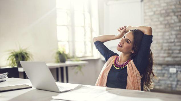 Das Bild zeigt eine junge Frau, die vor ihrem Laptop sitzt und ihren Arm dehnt.