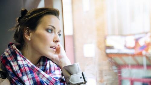 Eine Frau sitzt im Bus und blickt nachdenklich aus dem Fenster.