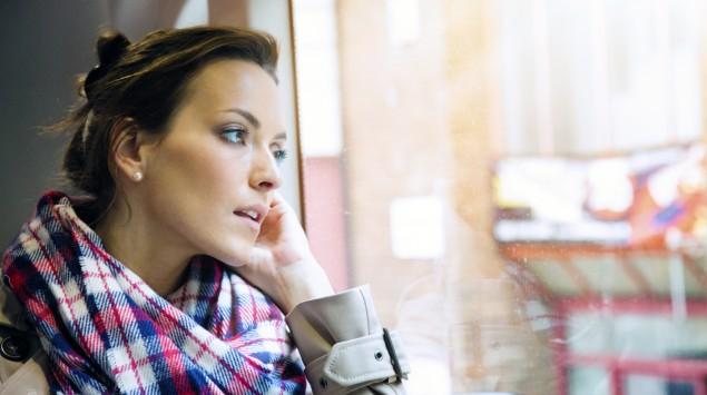 Eine junge Frau schaut mit leicht geöffnetem Mund aus dem Fenster: Mundgeruch bemerken die Betroffenen oft selbst nicht.