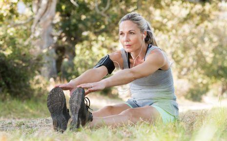 Eine Frau mittleren Alters sitzt mit langgestreckten Beinen auf einer Wiese und berührt mit beiden Händen ihre Zehenspitzen.