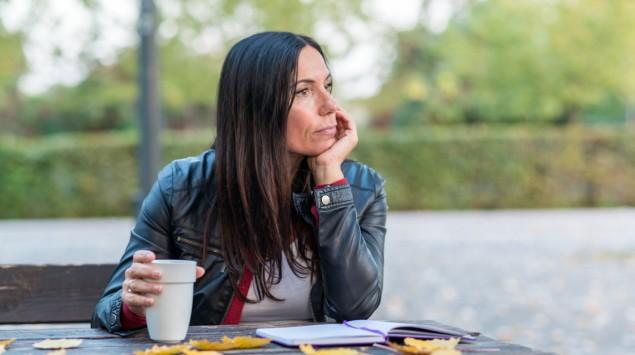 Eine Frau mittleren Alters sitzt an einem Herbsttag draußen an einem Tisch, vor sich ein aufgeschlagenes Notizbuch, in der rechten Hand einen Kaffeebecher haltend und mit der linken Hand ihren Kopf stützend.
