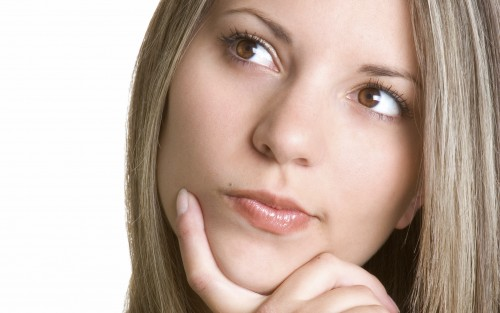 Eine junge Frau legt mit nachdenklichem Gesichtsausdruck den Finger ans Kinn.