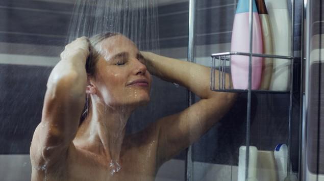 Eine Frau steht unter der Dusche.