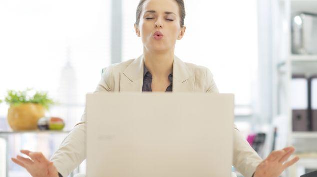 Das Bild zeigt eine junge Frau, die vor ihrem Laptop sitzt und ihre Finger abspreizt.