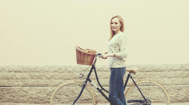 Eine Frau steht mit ihrem Fahrrad auf der Straße.