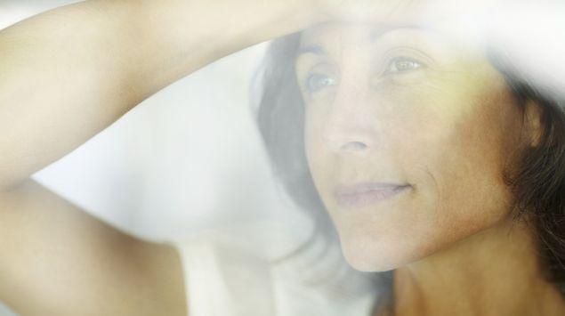 Eine Frau blickt nachdenklich durch ein Fenster.