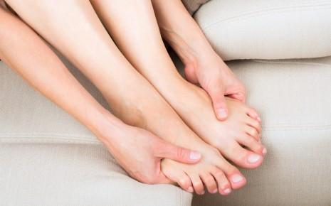 Polyneuropathie: Eine Frau sitzt in einer Sofaecke und umfasst ihre Füße mit den Händen..