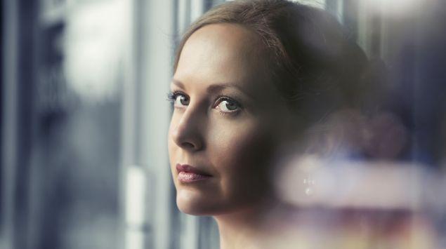 Eine Frau schaut nachdenklich aus dem Fenster.