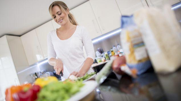 Eine Frau steht in der Küche und schneidet Gemüse klein.