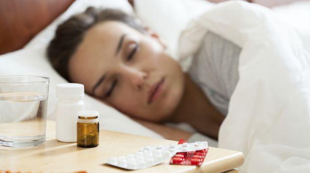 Eine Frau liegt krank im Bett und schläft.