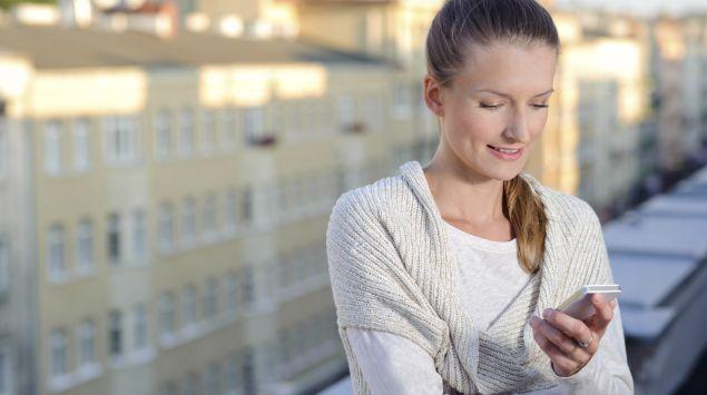 Eine Frau steht mit ihrem Mobiltelefon auf einem Balkon.