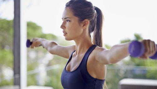 Eine junge Frau streckt beide Arme seitlich aus, sodass sich die zwei Kurzhanteln, die sie hält, in Schulterhöhe befinden.