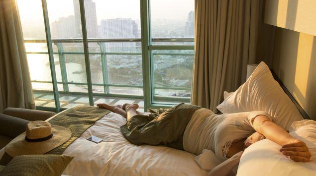 Eine Frau liegt bekleidet auf einem Bett im Hotelzimmer.
