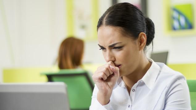 Ein Frau sitzt am PC und hustet.