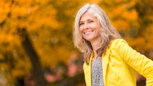 Zu sehen ist eine lächelnde Frau mittleren Alters vor Bäumen mit herbstlich verfärbtem Laub.
