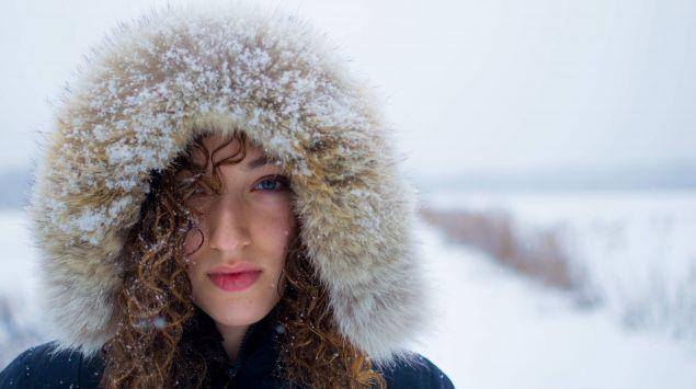 Das Bild zeigt eine junge Frau mit Winterjacke im Winter.