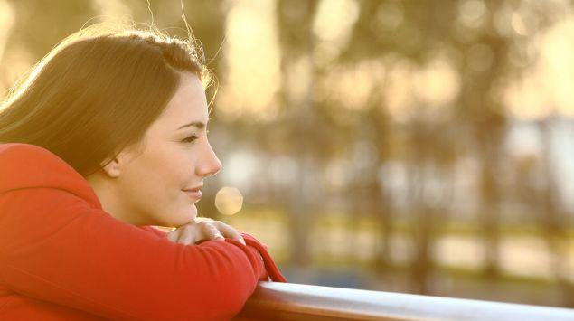 Eine Frau stützt sich auf ein Geländer und blickt optimistisch in die Ferne.