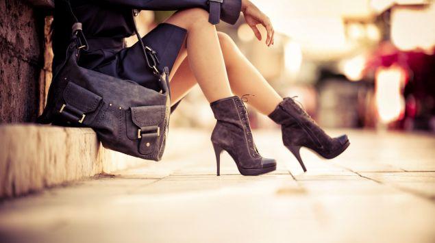 Eine Frau mit hochhackigen Stiefeletten und Handtasche sitzt auf einer Treppe.