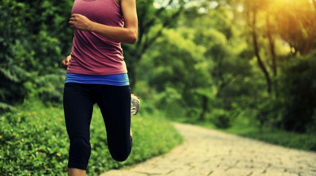 Eine Frau joggt durch einen Park.
