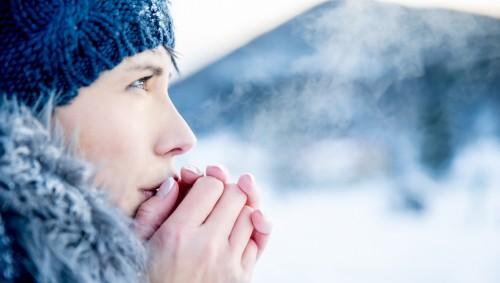 Eine winterlich gekleidete Frau wärmt ihre Hände durch Anhauchen.