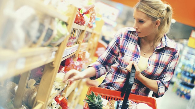 Eine junge Frau im Supermarkt hält einen Einkaufskorb in der Linken und greift mit der Rechten in ein Regal mit abgepackten Backwaren.