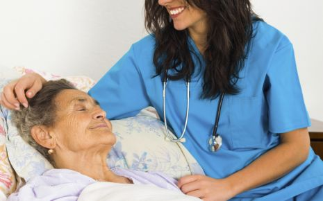Man sieht eine ältere Frau im Bett und eine Krankenschwester.